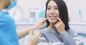 A patient pointing at her smile during a dental exam.