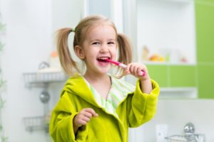 child smiling while brushing her teeth