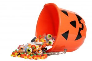 A bucket of Halloween candy being spilled.