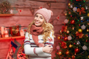 woman wearing winter warm clothes over Christmas decorations