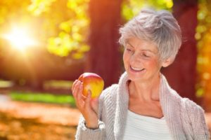 Smiling woman holding an apple with dentures in Pasadena