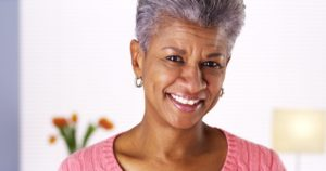 older woman smiling happy with new dentures