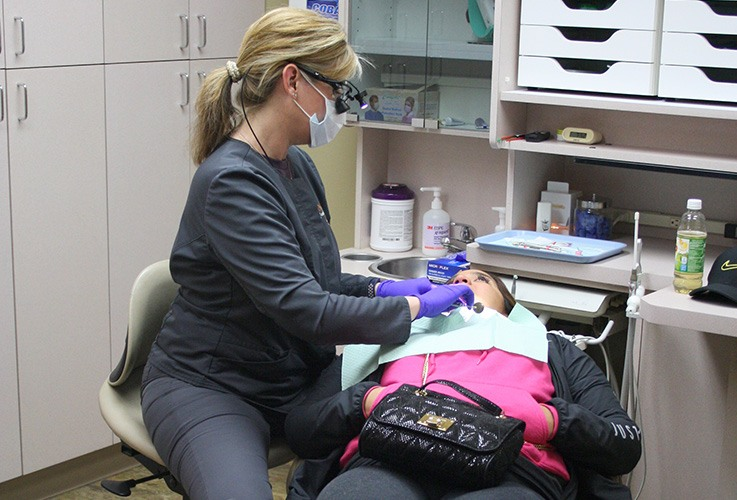 Team member examines dental patient
