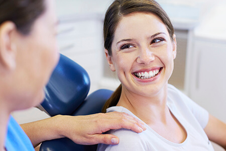 Young female patient smiling at dentist