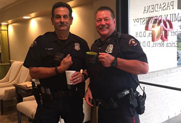 Two officers posing with coffees
