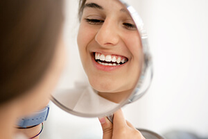 Young patient looking at smile in mirror