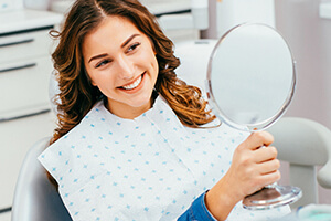 Young female patient examining mile in mirror