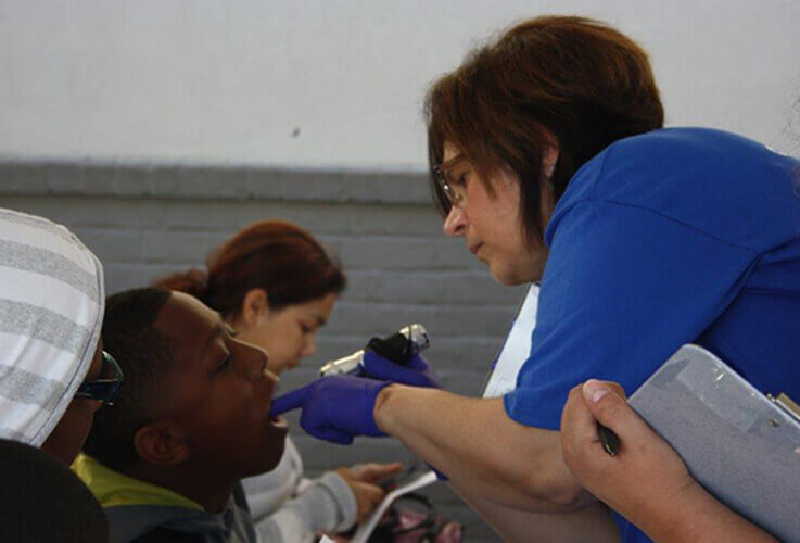 Team member examines young dental patient