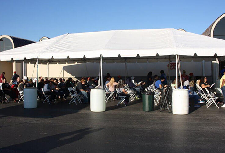 Group of patients waiting under large tent