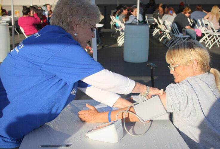 Dental assistant take patient's blood pressure