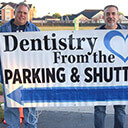 Volunteers hold Dentistry from the Heart parking sign