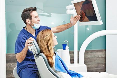 Patient and dentist look at intraoral photos