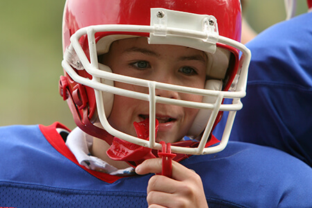 Young boy with red athletic mouthguard