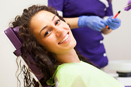 Smiling relaxed female patient in dental chair