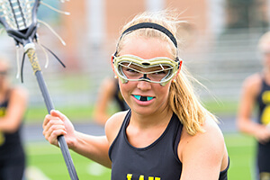Young girl wearing sportsguard playing lacrosse