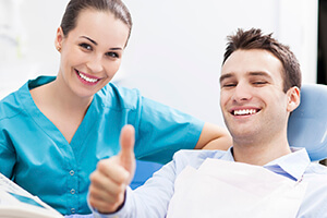 Smiling man giving thumbs up in dental chair