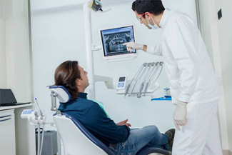 Dentist showing male patient his dental x-rays