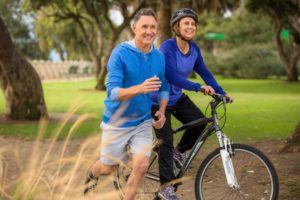 Couple smiling and exercising outside free of gum disease